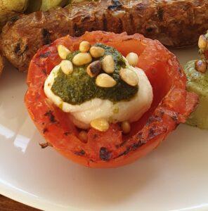 Gegrilde tomaten van de BBQ met vegan mozzarella, pesto en pijnboompitjes