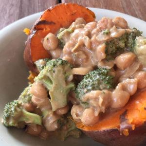 Gepofte zoete aardappel met broccoli en kikkererwten in kokos pindasaus