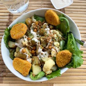 Geroosterde aardappel-bloemkool-linzen bowl met tahin-knoflooksaus